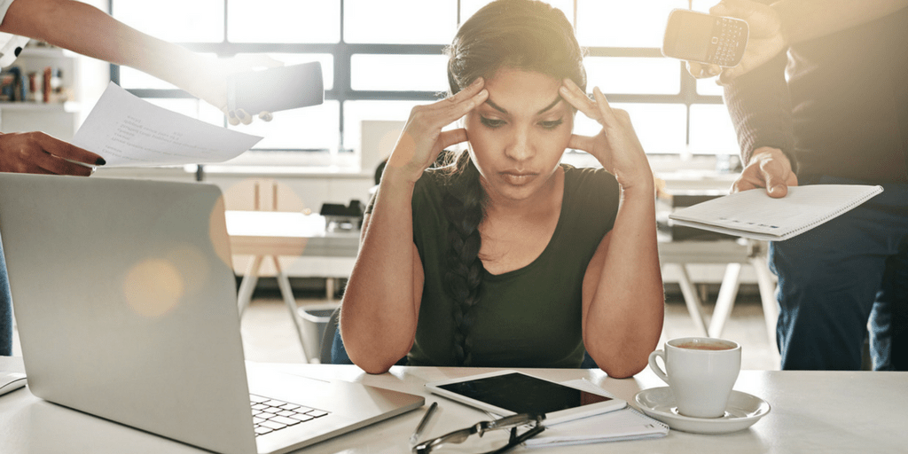 Office worker at laptop with distractions around her and looking frustrated